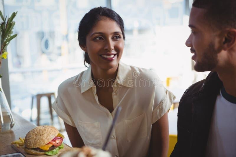 Glückliche junge Frau, die Mann im Café betrachtet lizenzfreies stockbild