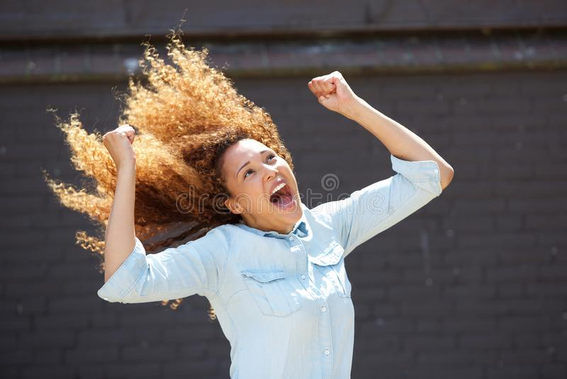 Glückliche junge Frau, die mit den Armen angehoben zujubelt lizenzfreies stockbild