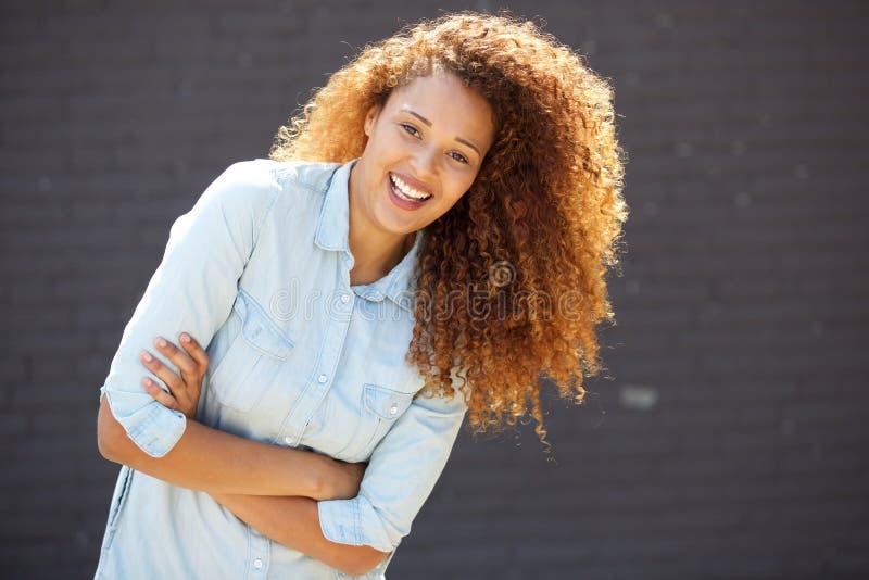 Glückliche junge Frau, die mit den Armen gekreuzt durch graue Wand lächelt lizenzfreies stockfoto