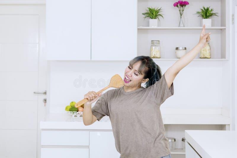 Glückliche junge Frau, die mit einer Spachtel singt lizenzfreies stockbild
