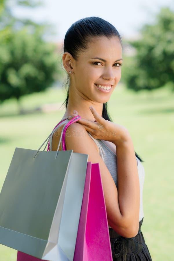 Glückliche junge Frau, die mit Einkaufenbeuteln lächelt stockfoto
