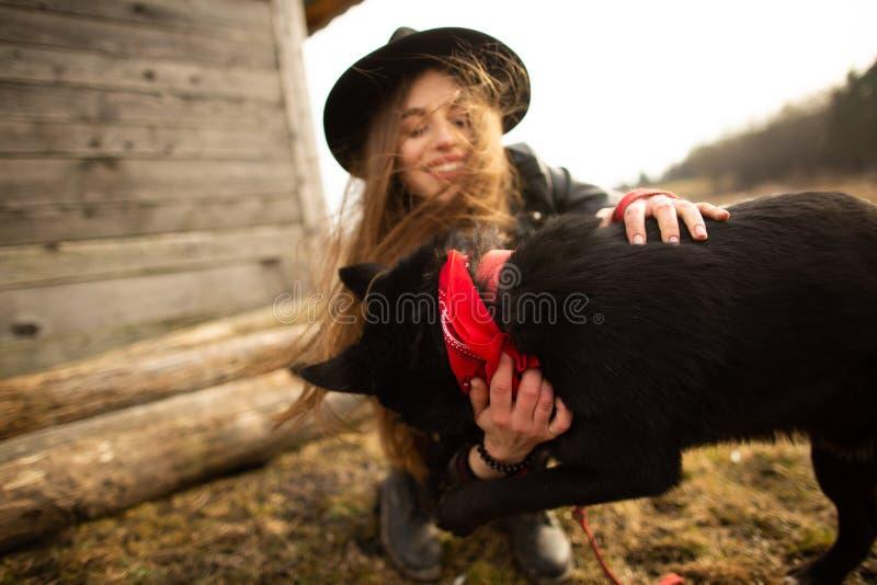 Glückliche junge Frau, die mit ihrem schwarzen Hund Brovko Vivchar im fron des alten Holzhauses plaing ist lizenzfreie stockfotos