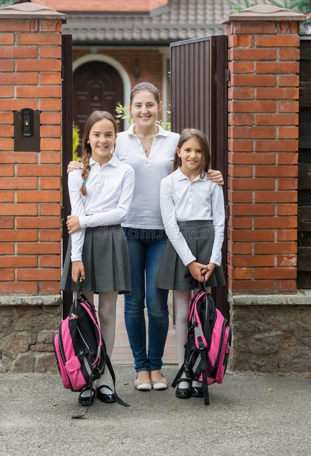 Glückliche junge Frau, die mit ihrer Tochter in der Schuluniform vor Haus aufwirft lizenzfreie stockfotografie