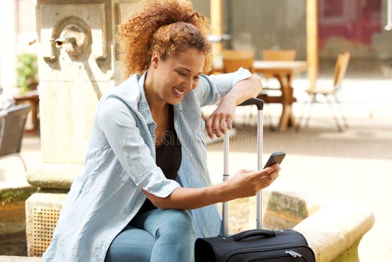 Glückliche junge Frau, die mit Koffer sitzt und Handy betrachtet lizenzfreies stockfoto