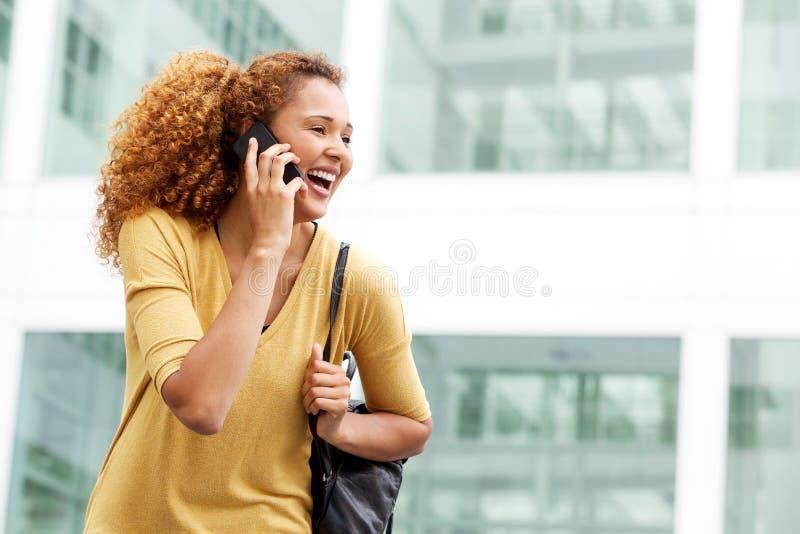 Glückliche junge Frau, die mit Mobiltelefon in der Stadt spricht lizenzfreie stockfotos