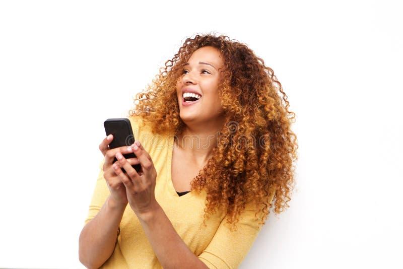 Glückliche junge Frau, die mit Mobiltelefon gegen weißen Hintergrund lacht lizenzfreie stockfotografie