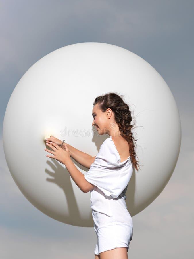 Glückliche junge Frau, die mit weißem Ballon steht stockfoto