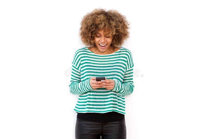 Glückliche junge Frau, die Mobiltelefon lächelt und betrachtet lizenzfreie stockbilder