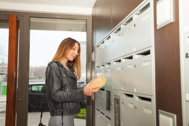 Glückliche junge Frau, die Paket in ihren Händen hält lizenzfreies stockfoto