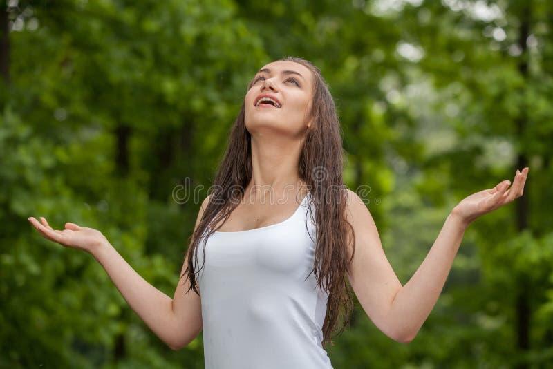 Glückliche junge Frau, die Regen im Sommer genießt lizenzfreies stockbild