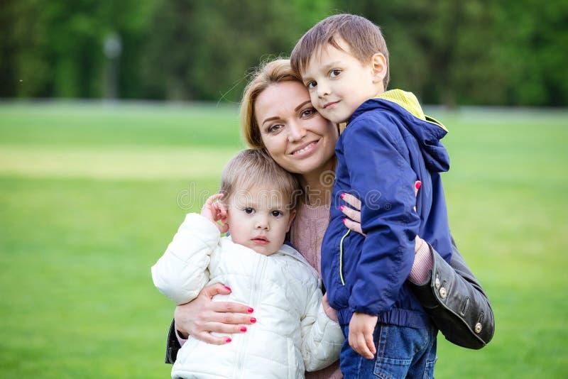 Glückliche junge Frau, die Söhne umarmt lizenzfreie stockfotos