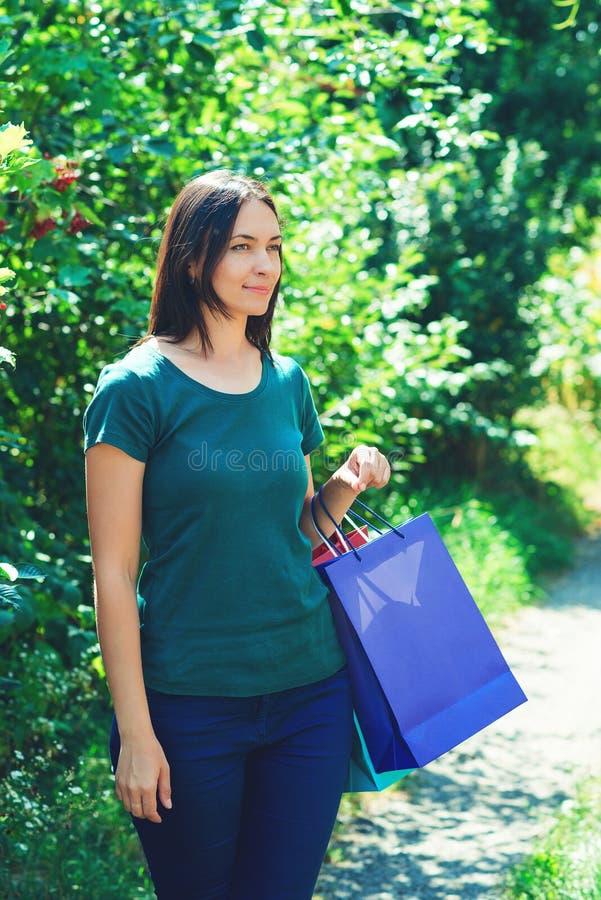 Glückliche junge Frau, die Saisonverkäufe mit den bunten Einkaufstaschen, beiseite schauend genießt Frauenart und weise Einkaufen lizenzfreie stockfotografie