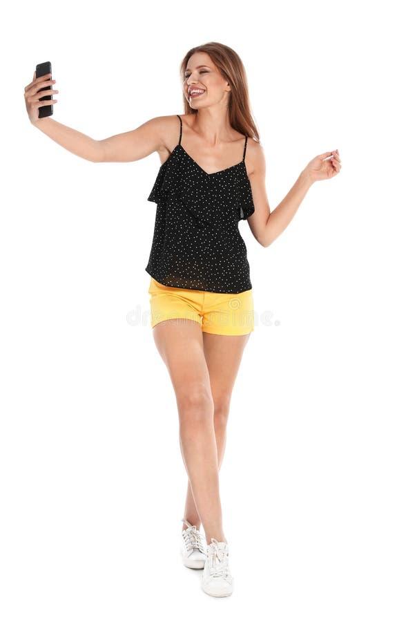 Glückliche junge Frau, die selfie auf Weiß nimmt lizenzfreies stockfoto