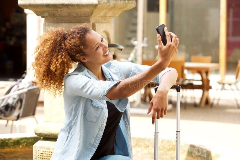 Glückliche junge Frau, die selfie draußen in der Stadt nimmt stockbild