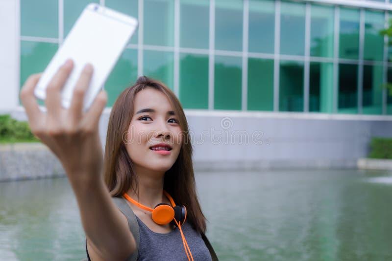 Glückliche junge Frau, die selfie mit Smartphone nimmt Schöner Asiat lizenzfreies stockfoto