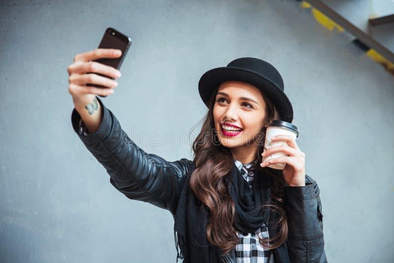 Glückliche junge Frau, die selfie nimmt Frau, die selfie Foto mit einem smarphone in der Stadtstraße macht stockfotos