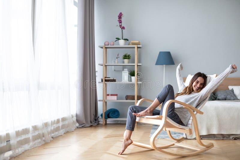 Glückliche junge Frau, die sich zu Hause entspannt stockfotografie