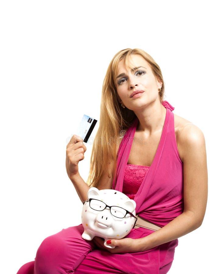 Glückliche junge Frau, die Sparschwein mit Brillen und Kredit hält stockbilder