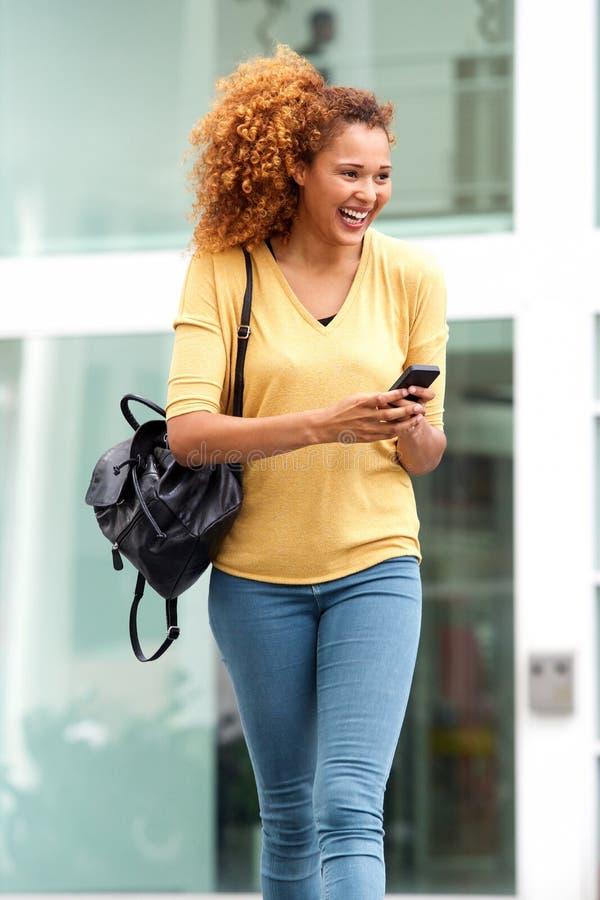 Glückliche junge Frau, die in die Stadt mit Handy und Tasche geht lizenzfreie stockbilder