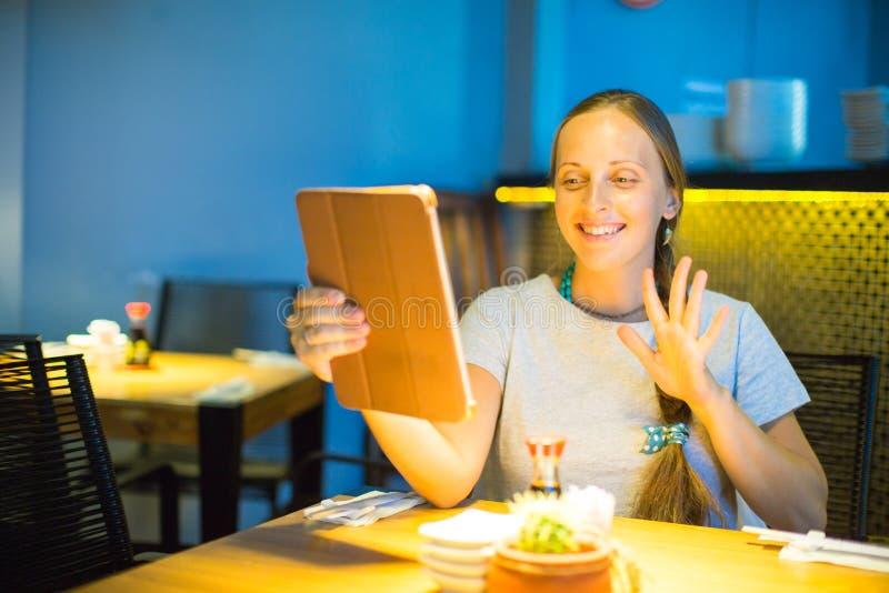 Glückliche junge Frau, die Tablet-Computer in einem Café verwendet stockbild