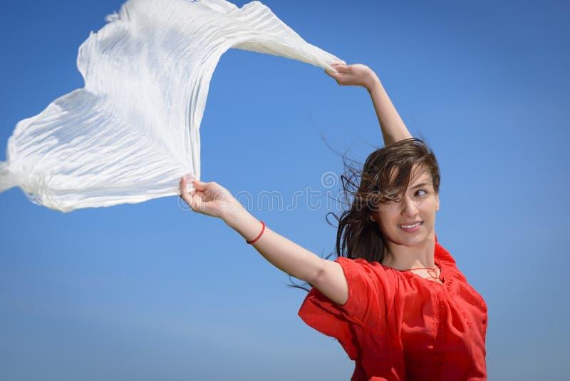 Glückliche junge Frau, die weißen Schal mit den geöffneten Armen ausdrücken Freiheit, Außenaufnahme gegen blauen Himmel hält lizenzfreie stockbilder