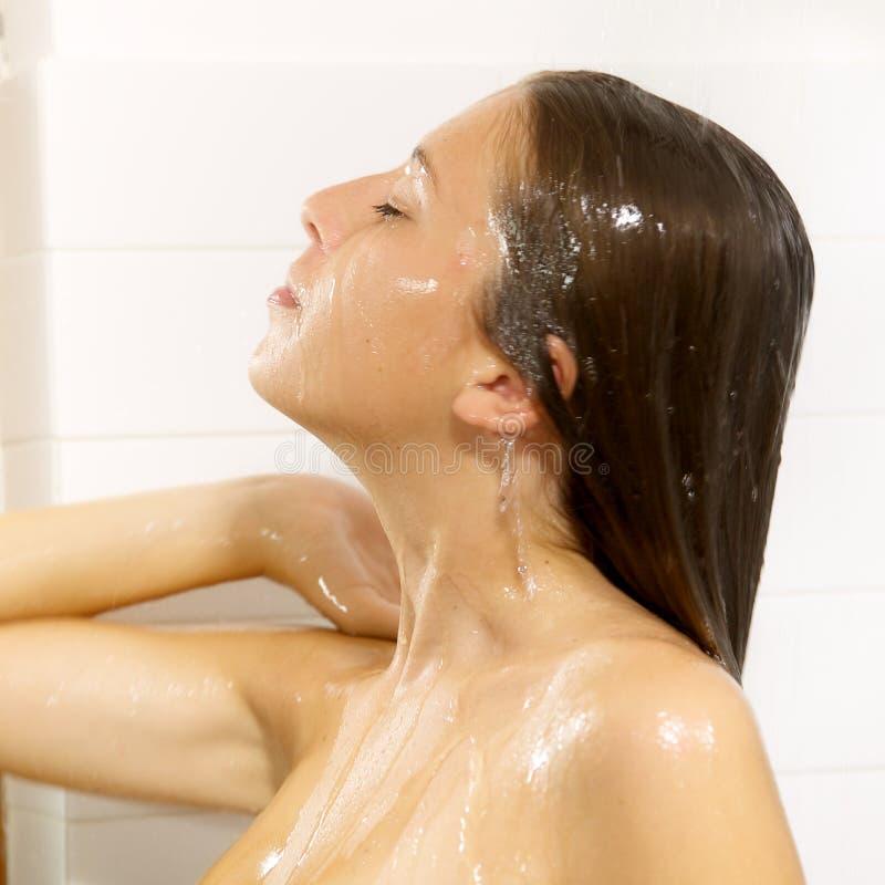 Glückliche junge Frau, die zu Hause Dusche nimmt stockfoto