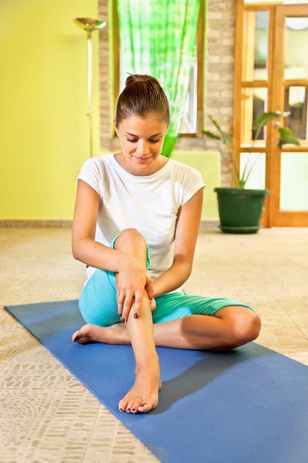 Glückliche junge Frau, die zu Hause Selbstmassage tut. lizenzfreie stockfotos