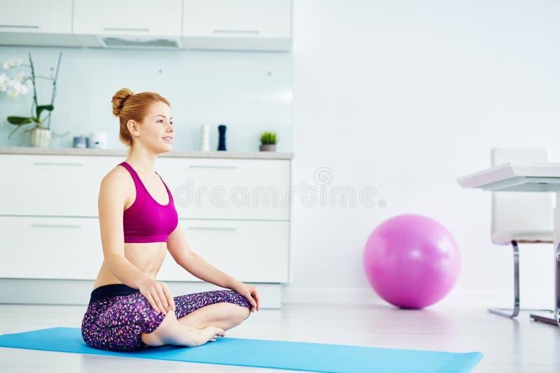 Glückliche junge Frau, die zu Hause Yoga tut lizenzfreie stockfotos