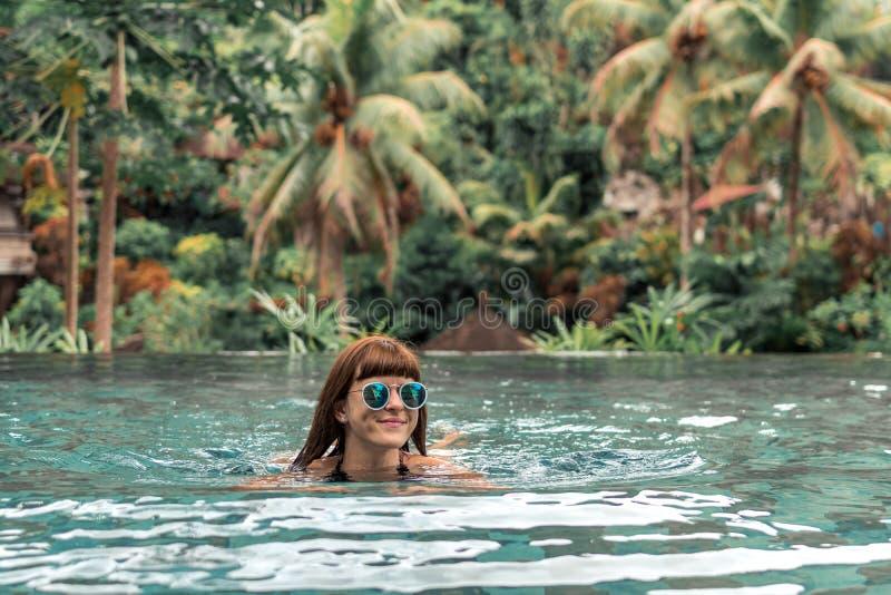 Glückliche junge Frau in einem tropischen Unendlichkeitspool Luxus-Resort auf Bali-Insel stockfotografie