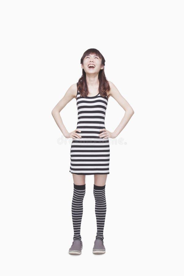 Glückliche junge Frau in gestreiftes Kleiderlächelndem oben schauen, Atelieraufnahme stockfoto
