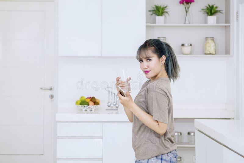 Glückliche junge Frau hält Telefon und Glas lizenzfreies stockbild