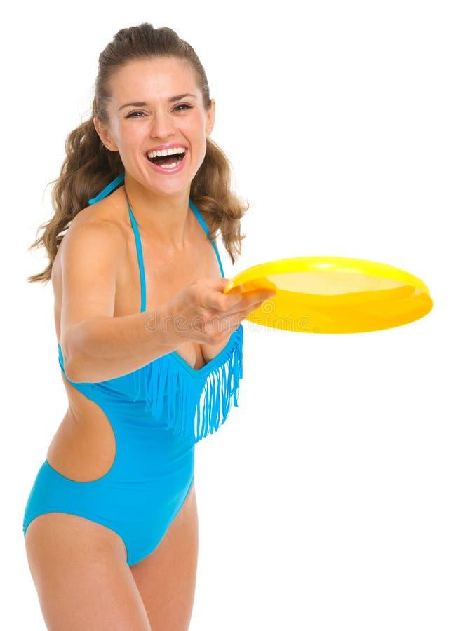 Glückliche junge Frau im Badeanzug, der mit Frisbee spielt stockfotos