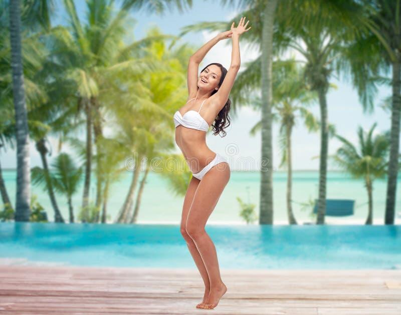 Glückliche junge Frau im Bikinitanzen auf Strand stockfotos