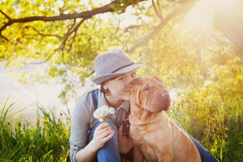 Glückliche junge Frau im Denimoverall und Hut mit einem Blumenstrauß des Löwenzahns ihren roten netten Hund Shar Pei auf dem Feld lizenzfreie stockbilder