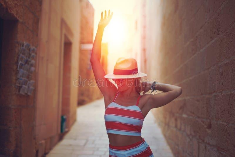 Glückliche junge Frau im Huttanzen im Sonnenuntergang auf altem Mittelmeer lizenzfreies stockbild