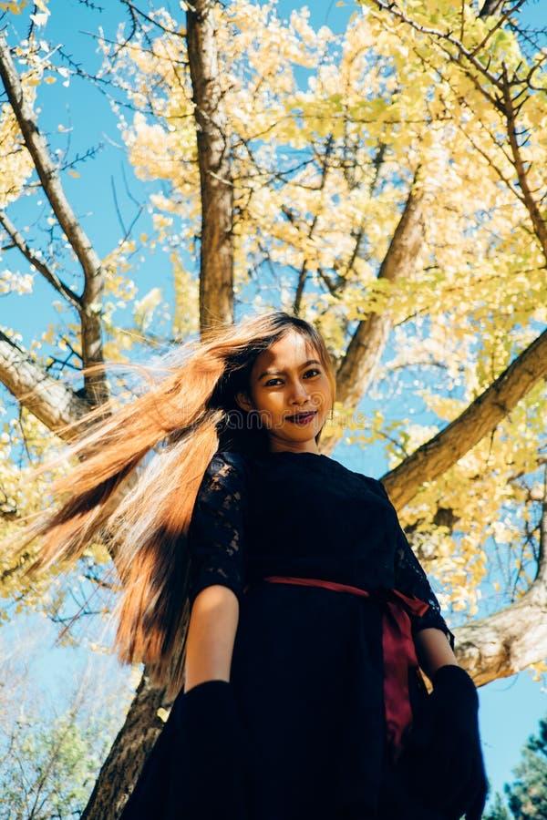 Glückliche junge Frau im Park am sonnigen Herbsttag, lächelnd Nettes schönes Mädchen in der schwarzen Retro- Kleiderherbst-Modear lizenzfreie stockfotos