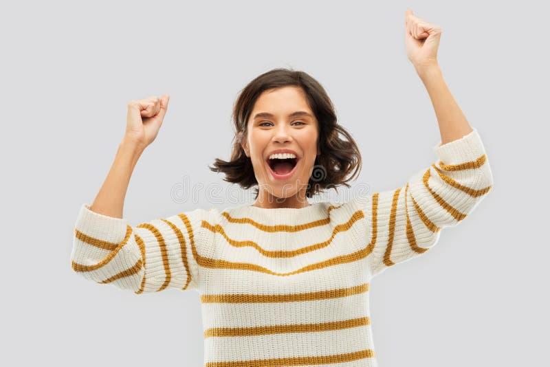 Glückliche junge Frau im Pullover Erfolg feiernd stockbild