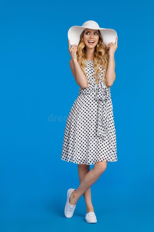 Glückliche junge Frau im Sommer-Kleid und in Sun-Hut schaut weg und Unterhaltung lizenzfreie stockfotos
