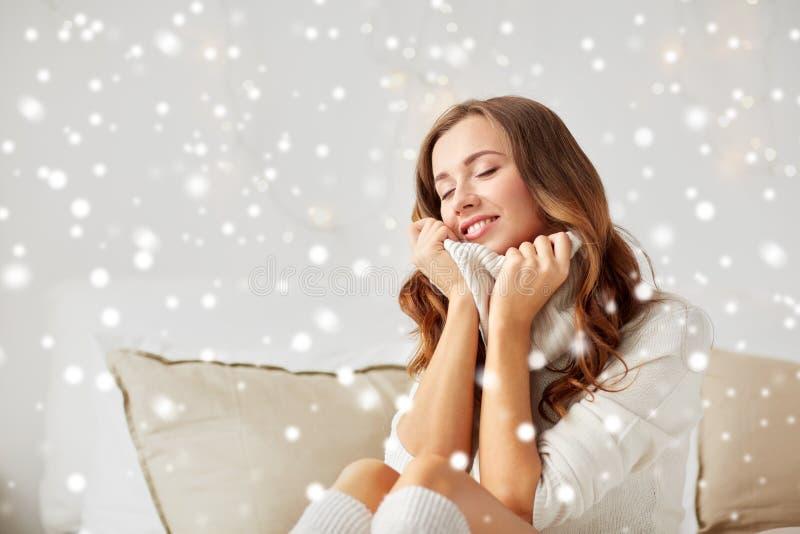Glückliche junge Frau im warmen Pullover zu Hause lizenzfreie stockfotos