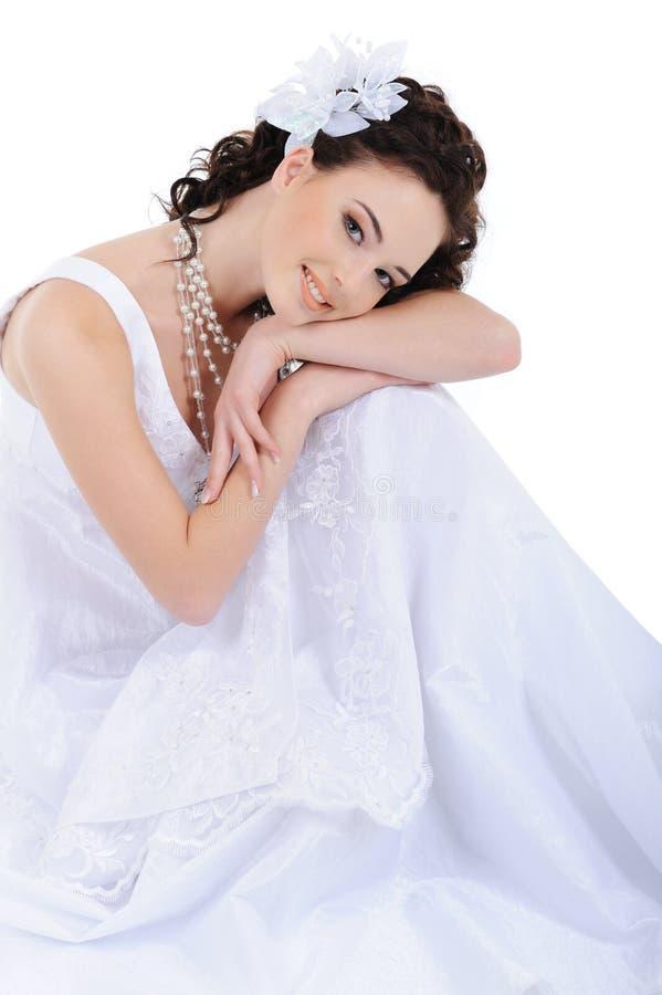 Glückliche junge Frau im weißen Hochzeitskleid stockfotografie