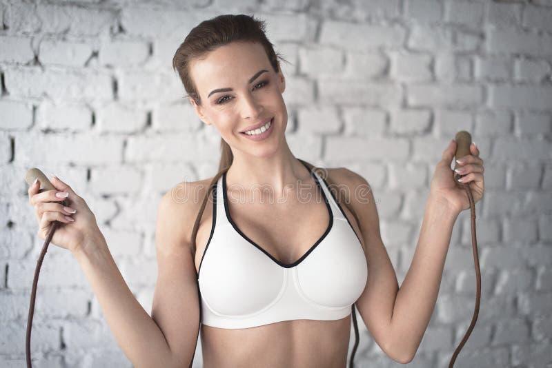 Glückliche junge Frau ist Sport-BH-Holdingseilspringen lizenzfreies stockbild