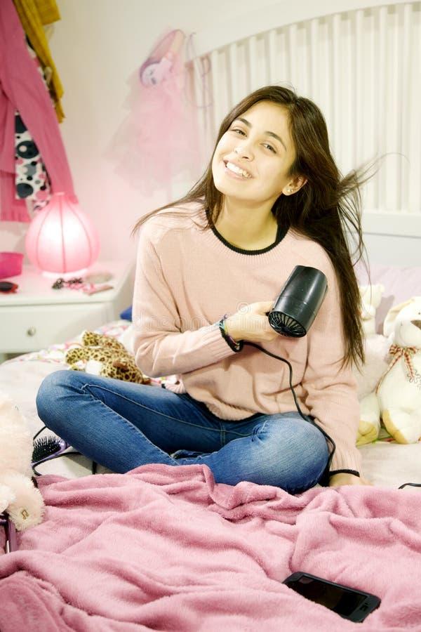 Glückliche junge Frau Latinas, die ihr langes schwarzes Haar trocknet, das auf dem Bett sitzt lizenzfreies stockbild