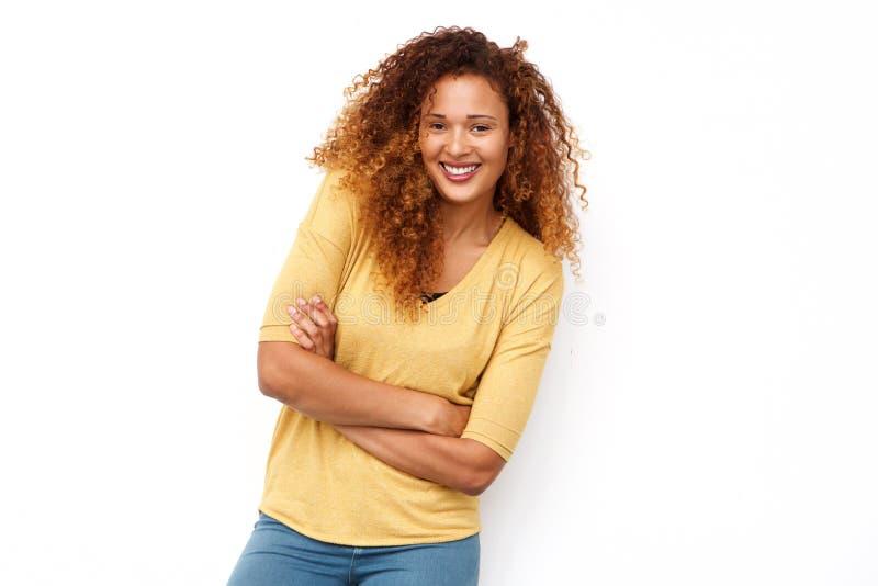 Glückliche junge Frau mit dem gelockten Haar, das gegen weißen Hintergrund aufwirft lizenzfreie stockfotos