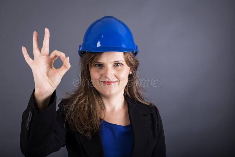 Glückliche junge Frau mit dem Hardhat, der okayzeichen zeigt stockfoto