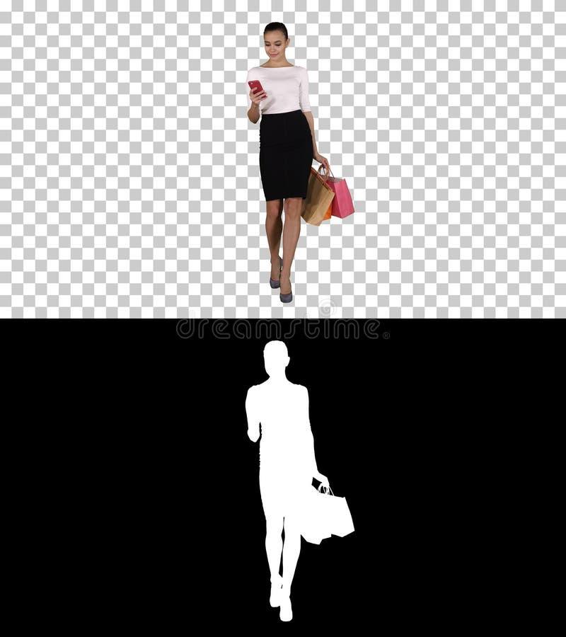 Glückliche junge Frau mit dem Smartphone, der Bild von ihren Einkaufstaschen, Alpha Channel macht lizenzfreie stockfotografie