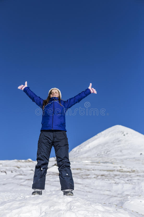 Glückliche junge Frau mit den Armen hob Stellung auf die Oberseite eines moun an stockfotografie