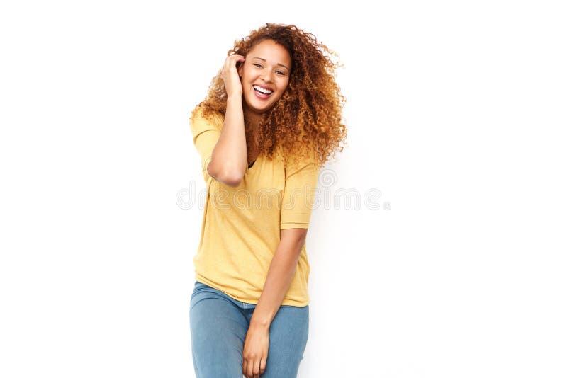Glückliche junge Frau mit der Hand im gelockten Haar gegen weiße Wand stockfotografie