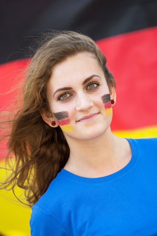 Glückliche junge Frau mit deutscher Flagge auf Backen auf dem Hintergrund stockfotografie
