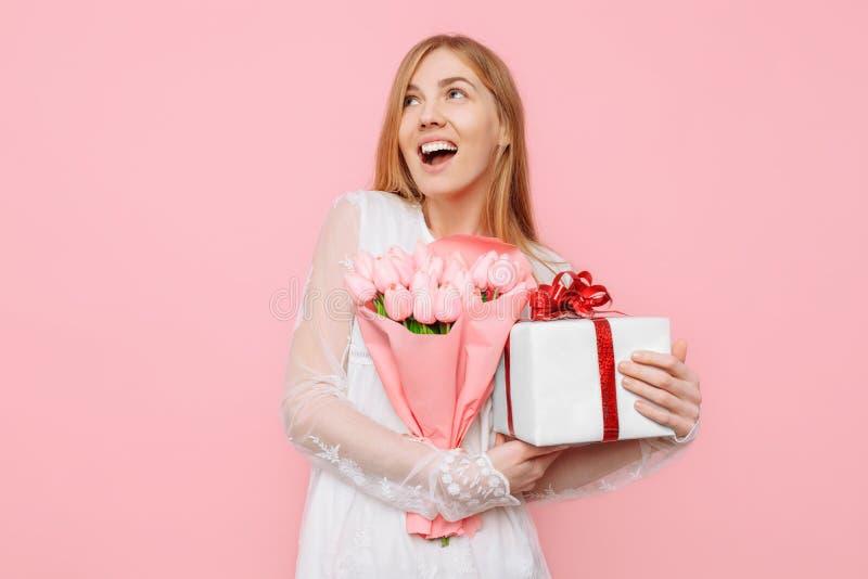 Glückliche junge Frau mit einer Geschenkbox und ein Blumenstrauß von Tulpen in ihren Händen Auf einem rosa Hintergrund Konzept, V lizenzfreies stockbild