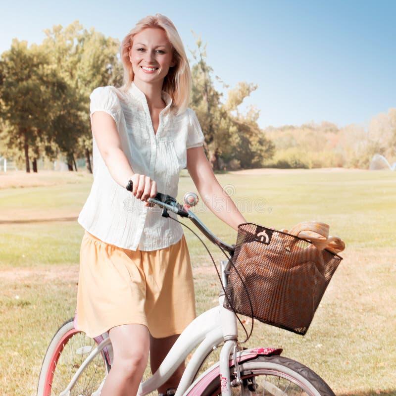 Glückliche junge Frau mit Fahrrad lizenzfreie stockfotografie